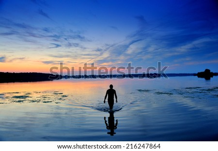 Man exiting water.Lake.Sunset.Nature, - stock photo