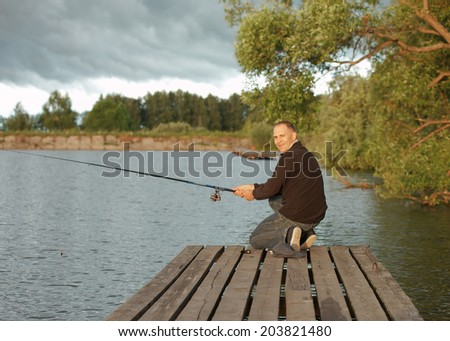 man fishing in a pond in a sunny day