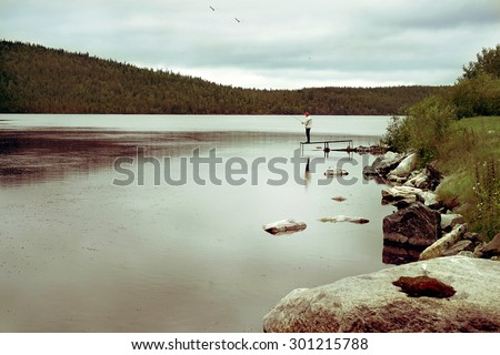Man fishink on the lake, peaceful view      - stock photo