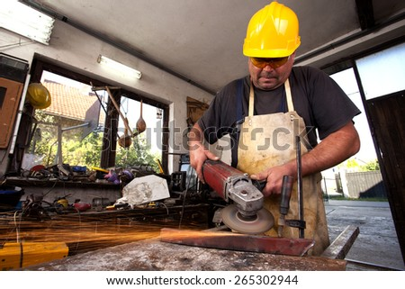 Man Grinding in workshop,shallow depth of filed - stock photo