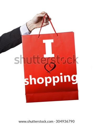 Man hand carrying and showing a red shopping bag isolated on white background announcing the motto I LOVE SHOPPING in consumerism , expending money addiction and shopaholic concept