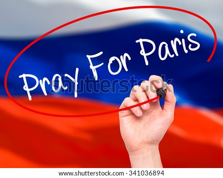 Man Hand Pray for Paris with marker on visual screen. Isolated on flag.  - stock photo