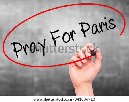 Man Hand Pray for Paris with marker on visual screen. Isolated on grey.  - stock photo