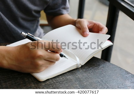 man hand write pen on blank notebook ,hand writing pen on paper page,hardworking for achievement business target concept, write idea by pencil.