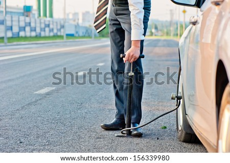 man in a business suit pumps hand pump wheel of a car - stock photo