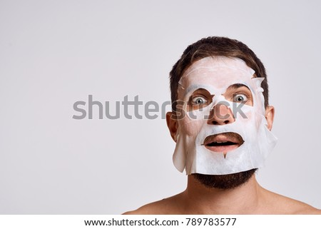 man in a cosmetic mask on a light background, skin care