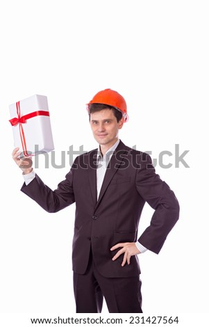 man in a helmet in a suit gives a gift white gift box with red ribbon bow, isolated over white background.
