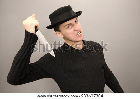 Man in hat holding knife on grey background
