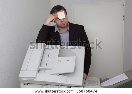 man in office near copier with a paper out of order on his face - stock photo