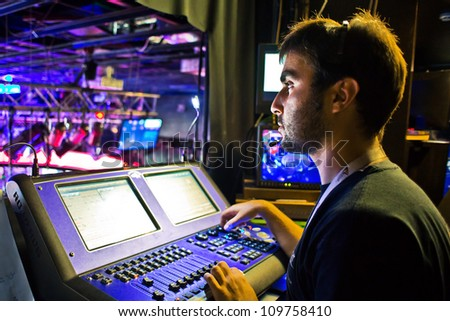 man in  studio working with sound and light mixer console - stock photo