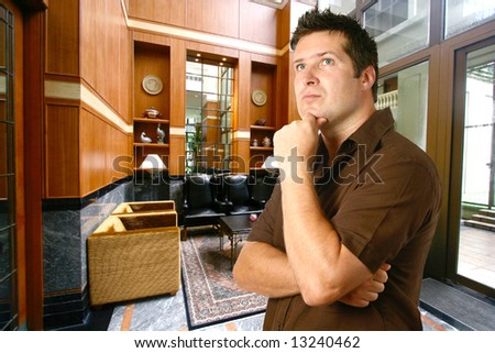 Man in thinking gesture against plush seating area with sofas and leather indoor setting. - stock photo