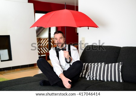 man in white shirt with bow-tie sitting in the living room with umbrella - stock photo