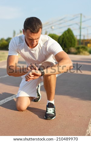 man looking at smartwatch heart rate a clock to measure performances of the training results at the stadium - stock photo
