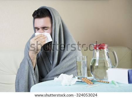 man On Sofa With Medicine And Glass Of Water Man  having flu takes pills, checking fever. flu, colds, fever - seasonal disease - stock photo
