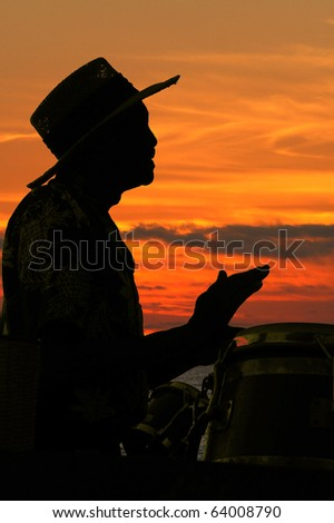 Man playing congos and bongos at a party with the sun setting in the backgound. The caribbean music and straw hat enhanced tropical theme being presented. - stock photo