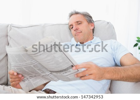 Man reading the newspaper on couch at home in living room