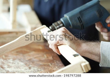 Man's arms drill lath in the workshop. - stock photo