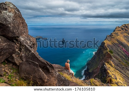 Man sitting on a cliff looking out over the sea at the rim of the crater of Rano Kao, Easter Island, Chile   - stock photo