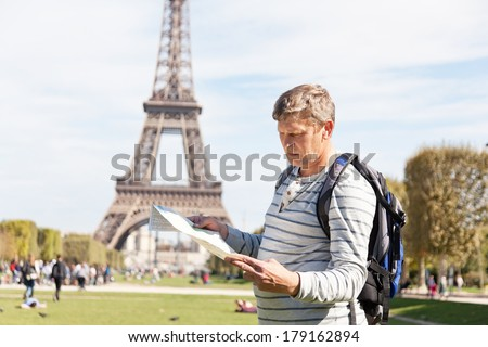 man - the traveler near the Eiffel Tower looks in a map of the city - stock photo