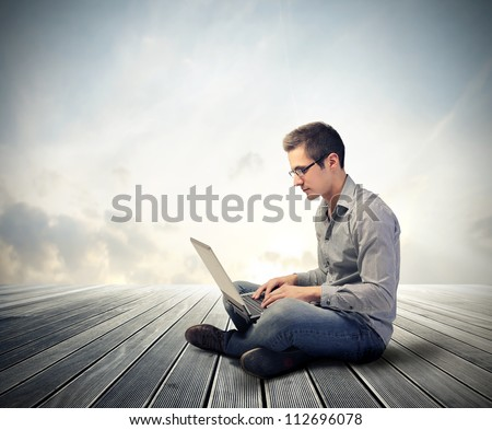Man using his laptop computer - stock photo