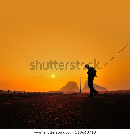 man walking alone during sunrise on a countryside road., Man walking at sunset on the mountain in a majestic summer sunset