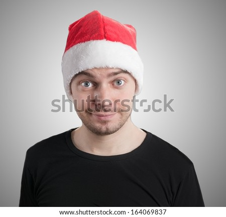 Man with a santa hat on grey background.