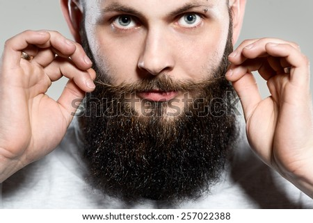 man with beard adjusting his mustaches while standing against grey background - stock photo