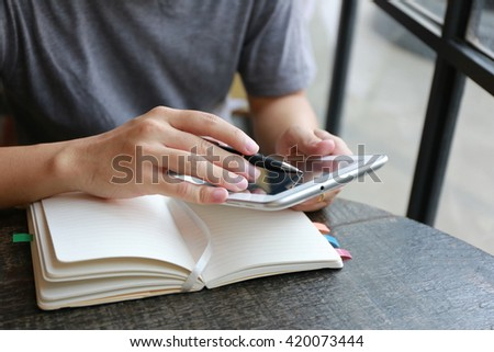 man working with tablet and book, internet of things , using mobile smart phone, Internet of things lifestyle with wireless communication and internet with smart phone. - stock photo