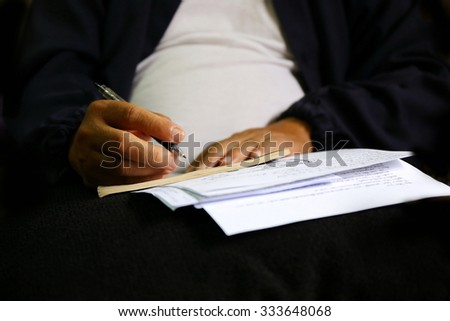 man write pen on document paper ,Close shot of a human hand writing something on the paper on the foreground, think and plan business.