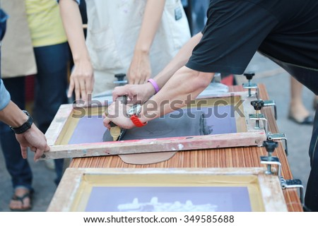 manual screen printing shirt, business owner hand press color on shirt screen print  for art work , shirt and cloths factory and shop.  - stock photo