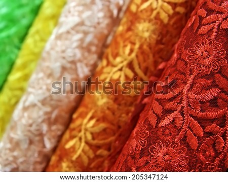 Many-colured guipure in textile shop - stock photo