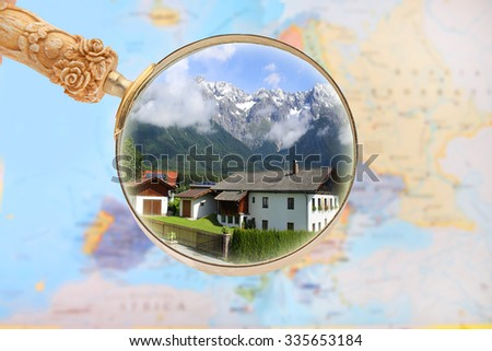 Map of Europe with magnifying glass looking in on  a house with the Alps Mountains in the background with sunny blue sky in Austria