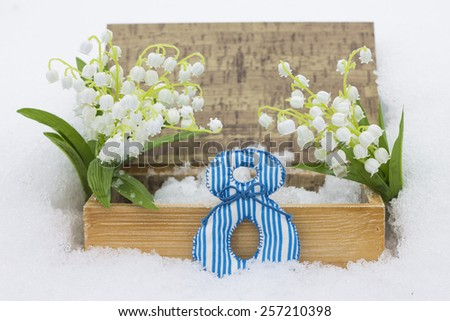8 March concept. Casket and lilies of the valley in snow - stock photo