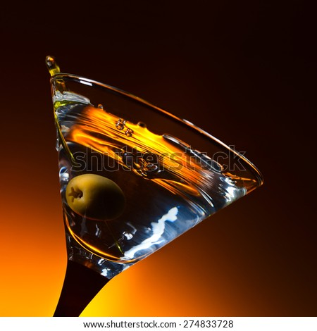 martini with green olive , focus on a berry