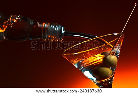 martini with olives ,focus on a berry - stock photo
