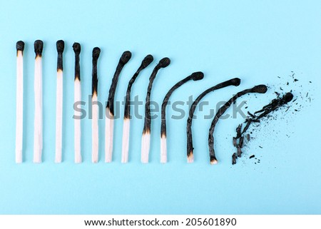 matches in different stages of burning, on color background - stock photo