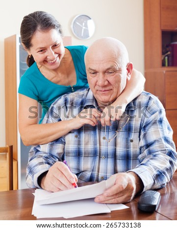 mature couple fills in paper documents together at home  - stock photo