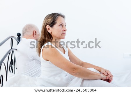Mature couple having quarrel on   bed in   bedroom. - stock photo