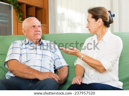 mature couple having serious talking in living room - stock photo