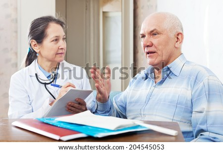mature doctor talks with sick senior man at near table with documents