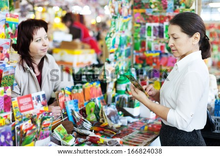 mature woman chooses packed seeds at store for gardener - stock photo