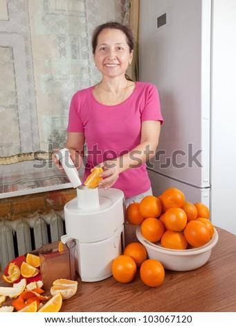 Mature woman making fresh orange juice in her kitchen - stock photo