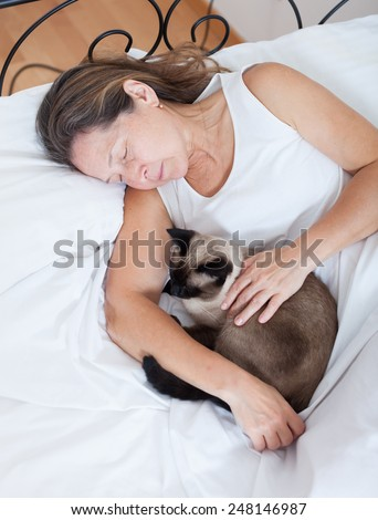 Mature woman sleeping in   embrace with   cat in   bedroom.