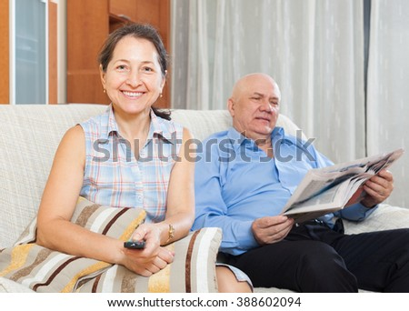 mature woman with TV remote against elderly man with newspaper in home interior - stock photo