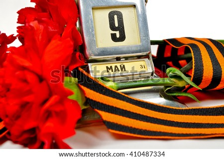 9 May card. Closeup of vintage metal desk calendar with 9 May date and George ribbon and red carnations -  Victory Day 9 May concept - stock photo