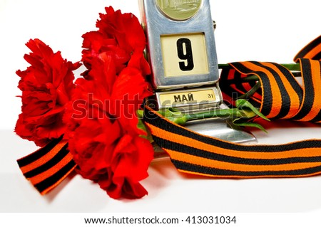 9 May card. Vintage metal desk calendar with 9 May date and George ribbon with red carnations bouquet -  Victory Day 9 May concept isolated on white background. Selective focus at the calendar.  - stock photo