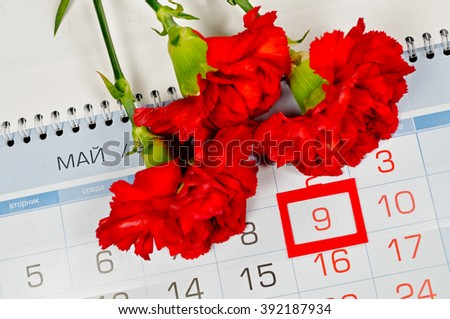 9 May concept. Bouquet of bright red carnations above the calendar with framed 9th May date - the day of USSR victory in Great Patriotic War in Russia. 9 May card.  - stock photo
