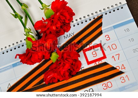 9 May concept. St George ribbon and red carnations above the calendar with 9th May date - the day of victory in Great Patriotic War in Russia - stock photo