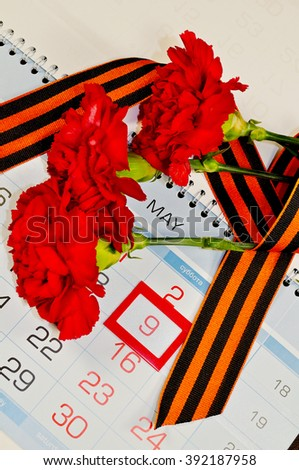 9 May concept. Victory Day card - three red carnations wrapped with George ribbon on the calendar with 9th May date- holiday that commemorates the victory of Soviet Union in the Great Patriotic War.  - stock photo