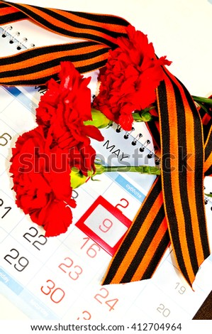 9 May concept. Victory Day card - three red carnations wrapped with George ribbon on the calendar with 9 May date- holiday that commemorates the victory in the Great Patriotic War. 9th May concept. - stock photo
